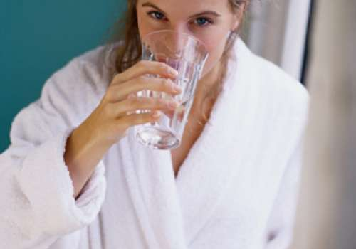 Woman drinking a glass of water in a bathrobe.