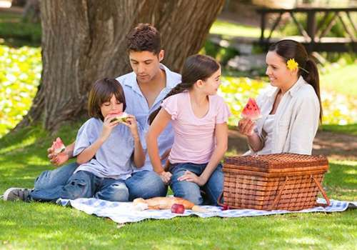 Family eating watermelon at an outdoor picnic.