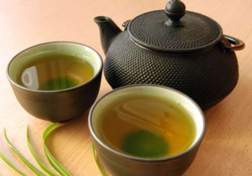 Tea pot with two cups of tea filled with green tea.