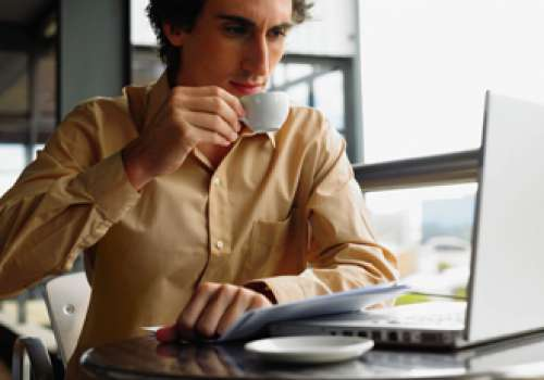 Man sitting at computer drinking coffee.