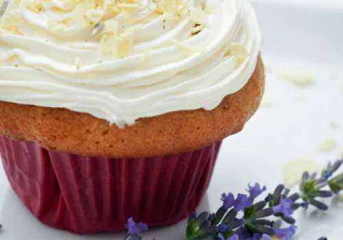 A frosted cupcake next to a sprig of lavender.