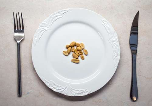 Place setting with handful of peanuts on white plate.