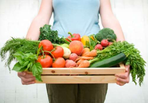 Woman holding wooden crate full of fresh produce