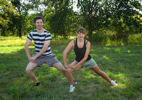 Young couple doing lunges outside.