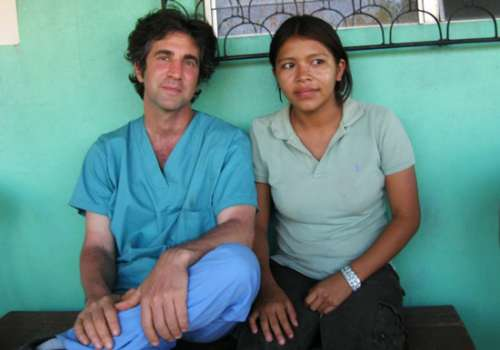 Daniel Fenyvesi, MSN ('07), RD, sits with another volunteer at a health clinic.