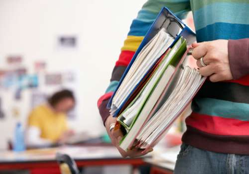 A student carries a stack of binders