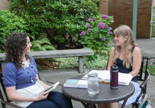 Two students study in campus courtyard