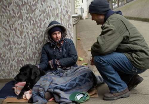 Man talking to homeless woman.