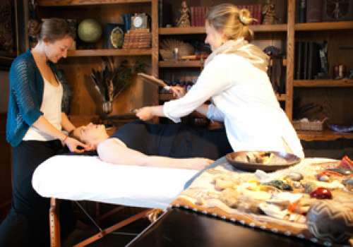 Woman on a massage table with two women performing healing motions.