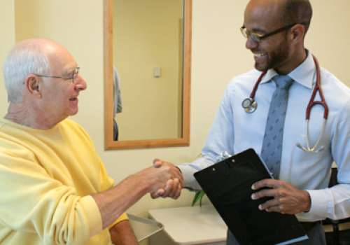 Naturopathic medicine student shakes hands with a senior patient.