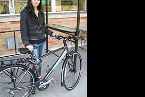 """A student standing with a """"Bastyr Bike"""""""