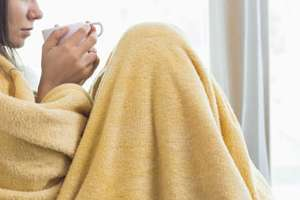Woman wrapped in blanket, suffering from flu.