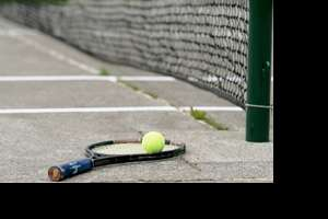 tennis racket and ball laying on a concrete court