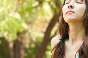 Woman taking deep breath outdoors.