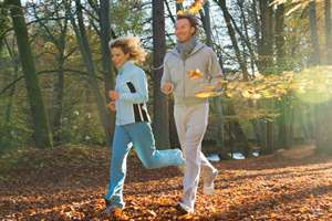 Couple running outdoors through autumn leaves.