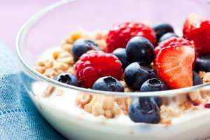 A bowl of yogurt with granola, strawberries and blueberries.