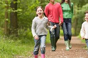 Happy family walking in woods.