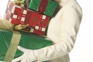 Smiling woman carrying holiday gifts.