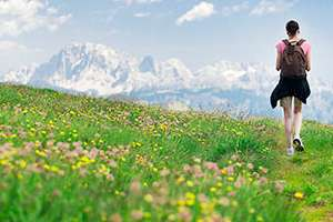Woman hiking in meadow toward mountains.