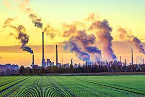 Factory smokestacks and crop fields