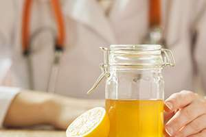 Doctor with a jar of honey and a lemon