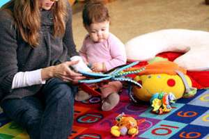 Student Erin Prasad reads to her daughter in the Parent Resource Center
