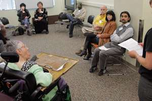 "Participants in the ""Human Library"" event sit in a circle listening to a speaker"