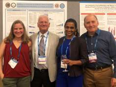 Researchers standing smiling in front of posters