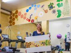 Kelly Buechel holds a smaller version of the mural she designed in the Bastyr University Student Fitness Room.