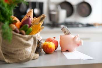 Bag of fruits and veggies with piggy bank