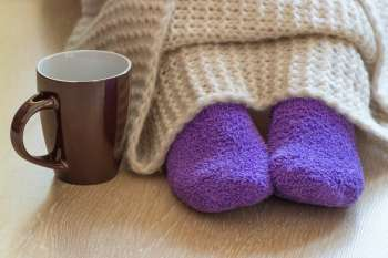 feet under blanket with mug