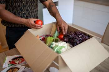 Person opening delivery box of food holding a tomato
