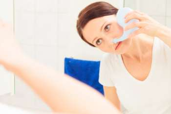 Woman using neti pot in bathroom