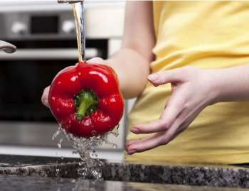 A woman rinses a red bell pepper under the faucet.