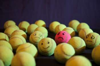 Tennis balls with happy and sad faces