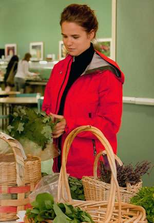 Woman in red coat standing and holding and looking at plants
