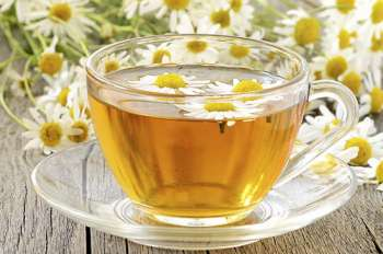 Glass teacup with tea and chamomile flowers.