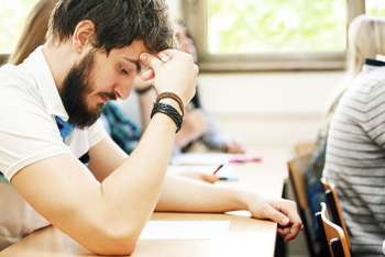Stressed student studying in class.
