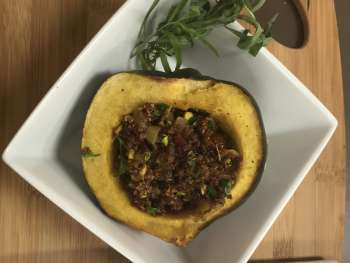 Plate with roasted acorn squash with cranberry quinoa stuffing