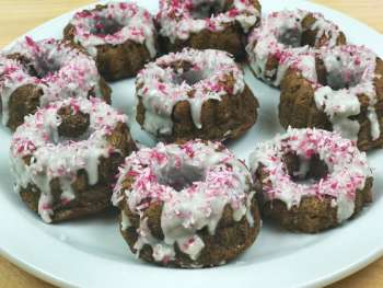 Plate of donuts with white frosting and pink sprinkles