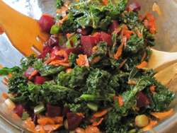 beet and kale salad with wooden salad tongs