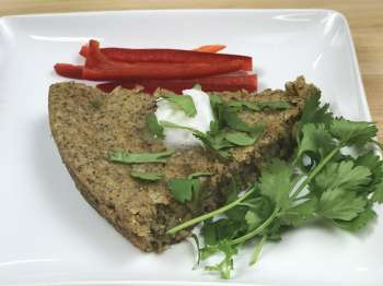 Vegan,gluten-free cornbread slice with herbs and red bell peppper slices