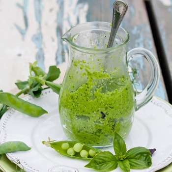 Green Pea Pesto in a jar garnished with green peas and basil.