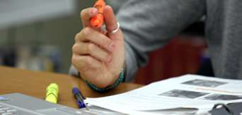 A closeup of a woman's hand holding a marker and studying.