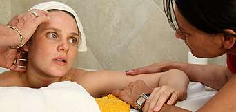 A doula comforts a woman in labor in a tub.